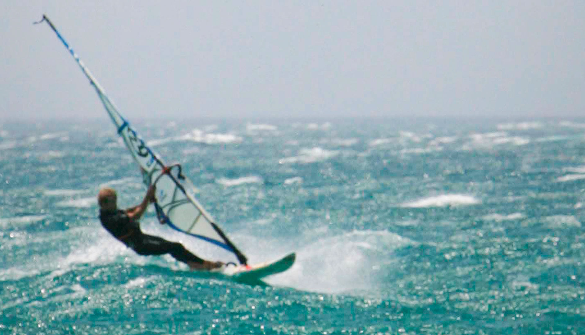 Two people kitesurfing and windsurfing in Tarifa.